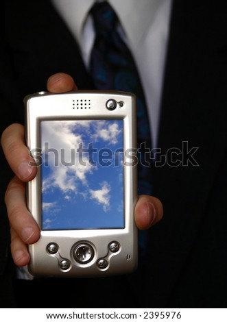businessman holding a pda with blue cloudy sky on the screen
