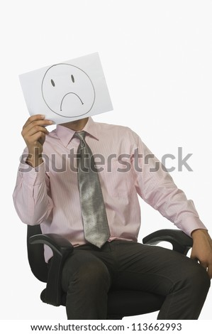 Businessman holding a piece of paper in front of his face with a sad on it