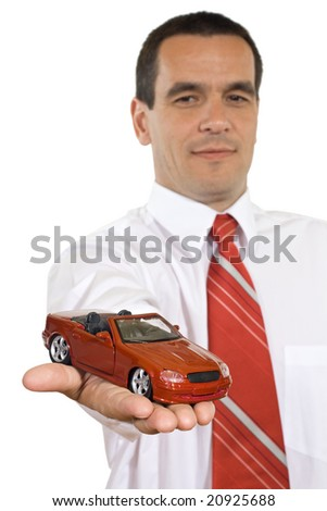 Businessman holding a red toy car in the hand - isolated