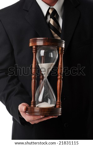 Businessman holding a sand timer isolated against a white background