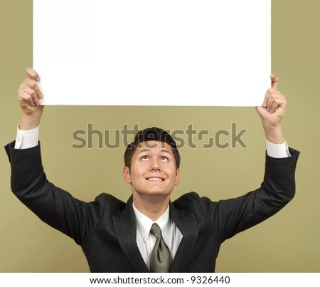 Businessman holding a sign that is easily expandable for copy and smiling