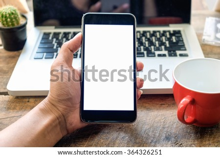 businessman holding a smart phone on wood table at office