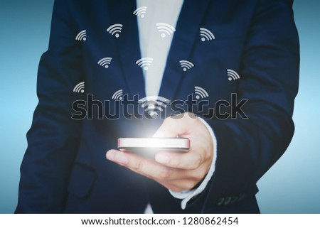 Businessman holding a smartphone with WiFi icon.Network technology internet concept.