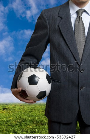 businessman holding a soccer ball , concept for sport as business