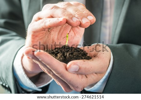 Businessman holding a sprouting seedling in fertile earth cupped in the palm of his hand in a conceptual image of environmental awareness or business startup.