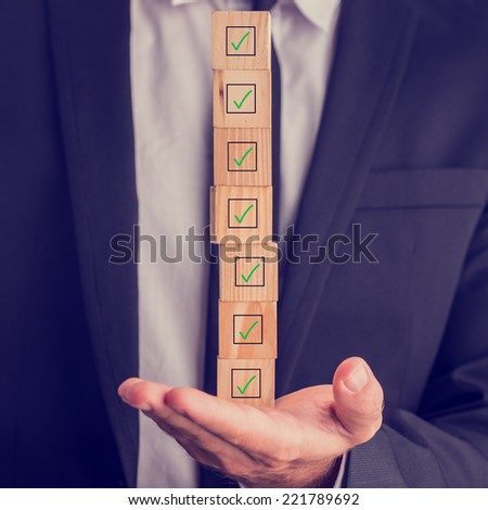 Businessman holding a stack of checked boxes marked on wooden cubes balanced on his hand conceptual of quality, completion, approval or voting.