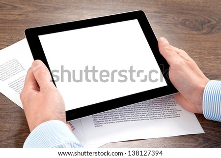 businessman holding a tablet computer with isolated screen on the table with documents