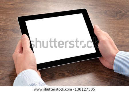 businessman holding a tablet computer with isolated screen  over the villages table