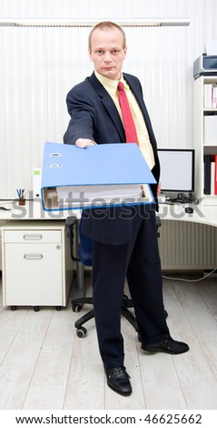 Businessman holding a thick dossier in his outstretched arm