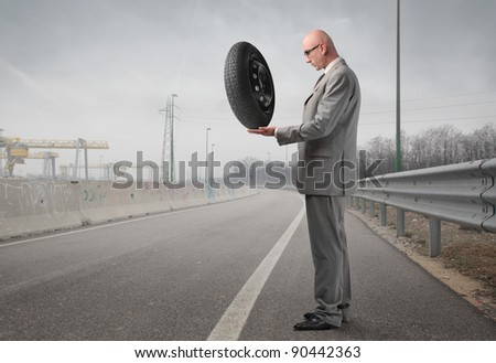 Businessman holding a tire on a street