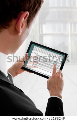 Businessman holding a touchpad pc, one finger touches the screen and writes an e-mail