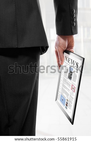 Businessman holding a touchpad pc with an electronic newspaper