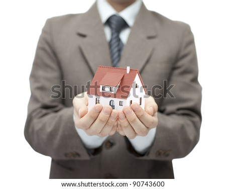 Businessman holding a toy house