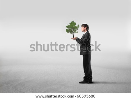 Businessman holding a tree in his hands