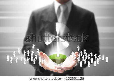businessman holding a wind turbine with people.