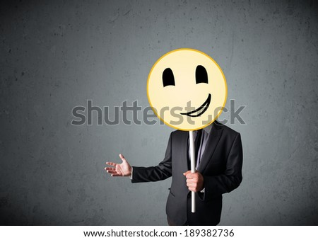 Businessman holding a yellow smiley face emoticon in front of his head #189382736