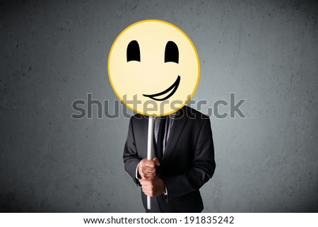 Businessman holding a yellow smiley face emoticon in front of his head #191835242