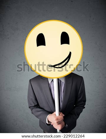 Businessman holding a yellow smiley face emoticon in front of his head #229012264