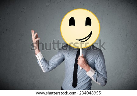 Businessman holding a yellow smiley face emoticon in front of his head #234048955