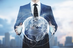 Businessman holding abstract digital globe on blurry city background. Communication concept. Double exposure