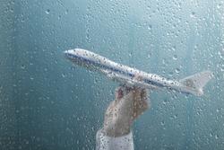 Businessman holding airplane behind wet window