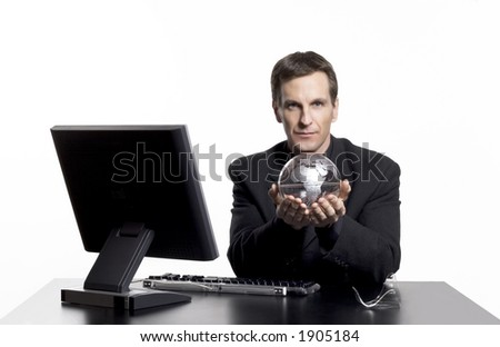 Businessman holding an earth globe at his desk.