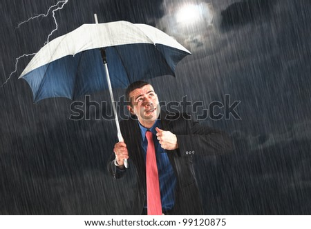 Businessman holding an umbrella in the storm