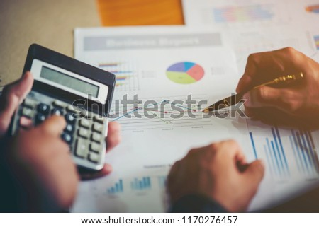 Businessman holding and analyzing investment chart working in office. Business work concept.
