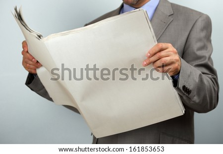 Businessman holding and reading a blank newspaper with copy space