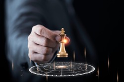 Businessman holding and throwing golden king chess to virtual target dart board. Setup objectives and target for business investment concept.