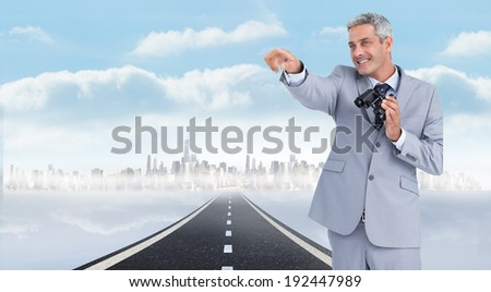 Businessman holding binoculars and pointing out something against open road background
