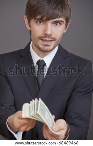 businessman holding bunch of dollars in his hands