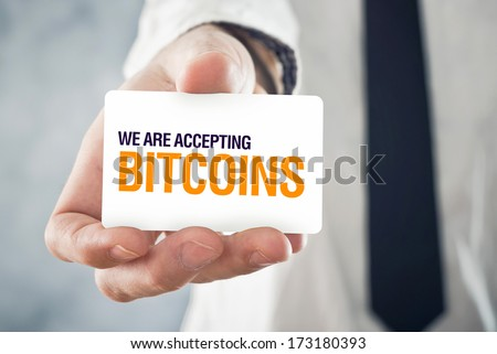 Businessman holding card with title WE ARE ACCEPTING BITCOINS. Selective focus on card and fingers.