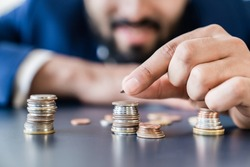 Businessman holding coins euro dollar cents counting money bills, making savings, accounting and managing currency for nest egg, mortgage loan , investments and dividends. Finance and economy concept