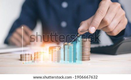 businessman holding coins putting in glass. concept saving money for finance accounting to arrange coins into growing graphs concept. Foto stock ©