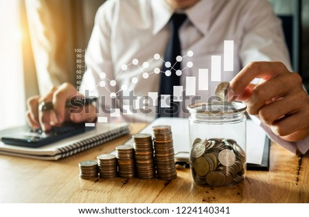 businessman holding coins putting in glass with using smartphone and calculator to calculate  concept saving money for finance accounting with VR icon  Foto stock ©