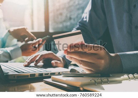 Businessman holding credit card and using laptop. Making payment while online shopping. E-commerce and modern technology concept