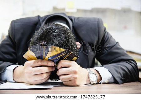 Businessman holding credit cards thinking seriously about payment loan problem - people with personal financial crisis concept
