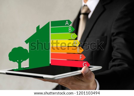 Businessman holding digital tablet and looking at house efficiency rating. Detail of house efficiency rating on digital tablet screen. Concept of ecological and bio energetic house. Energy class.