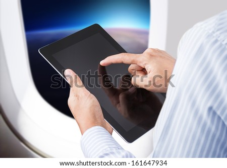 Businessman holding digital tablet in airplane with horizon background