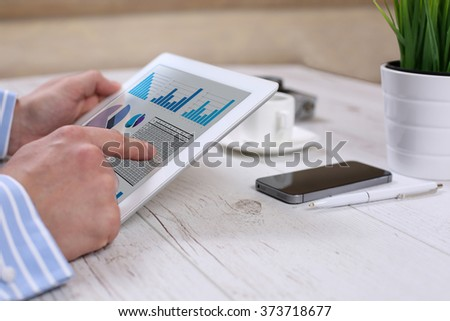 Businessman holding digital tablet showing charts and graph, analysis business, statistics concept. #373718677
