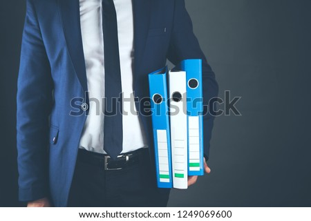 Businessman holding document ring binder