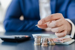 Businessman holding euro cents coins dollar bills on table with pile of coins and banks calculator, managing dividing money to save and invest it to make income. Saving money and investing concept.