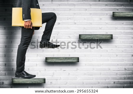 businessman holding files climbing stairs on brick wall