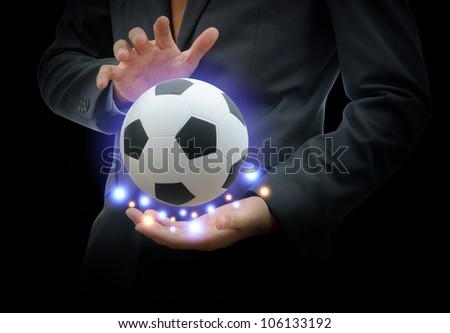 Businessman holding football isolated on black