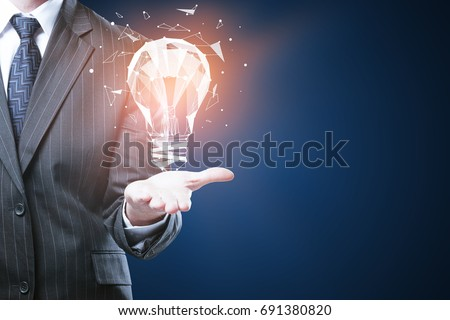 Businessman holding glowing polygonal lamp on blue background with copyspace. Innovative ideas concept