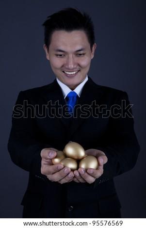 Businessman holding golden eggs - investment concept