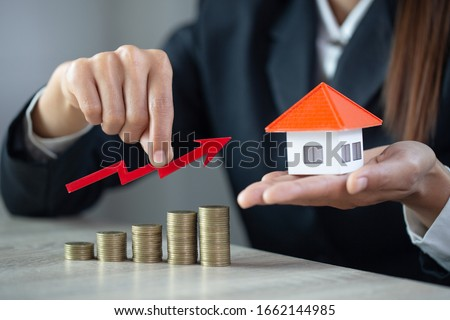 Businessman Holding  Graph Over The Increasing House Miniature, Real estate investment,investment mortgage finance and home loan business, growth and money.