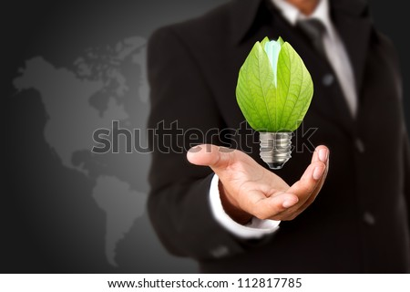 Businessman holding green light bulb, concept of saving energy