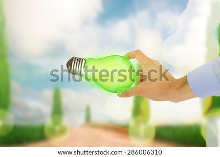 Businessman holding hand out in presentation against road leading out to the horizon